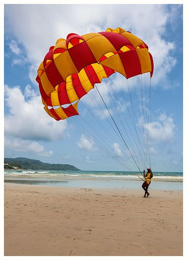 Man on the beach with a parasail getting ready to take off